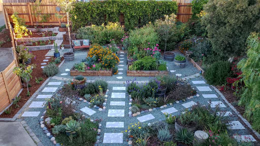A view of the Homestead and Chill front yard garden, as seen from the roof looking down, almost like a drone shot. The pathways between the raised garden beds and flower planting areas form two large peace signs. There is no grass. It is an edible oasis, and a certified wildlife habitat!