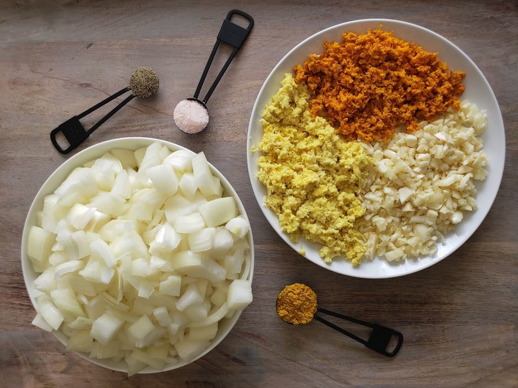 "The ""wellness trifecta"" of turmeric, ginger, and garlic are all chopped up on a plate on the right. Diced onions are piled in a bowl on the left. Around the plate and bowl, measuring spoons full of turmeric powder, black pepper, and salt are sitting."