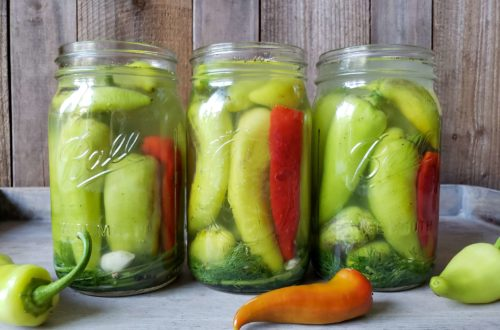 Three jars of pickled peppers in a row, full of mostly yellow-green banana peppers and few hot red ember chilis
