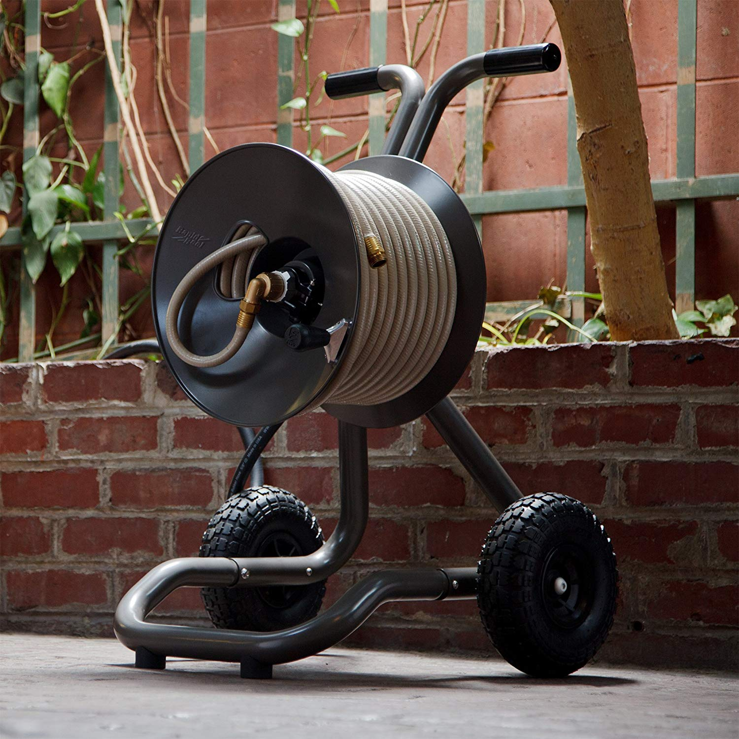 A hose reel is shown, it has two wheels and handles that are in the shape of a T. There is a wall of bricks in the background with a tree and some vines.